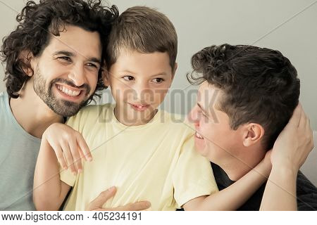 Cheerful Gay Fathers And Son Sitting On Couch Together And Hugging Each Other. Front View. Happy Fam