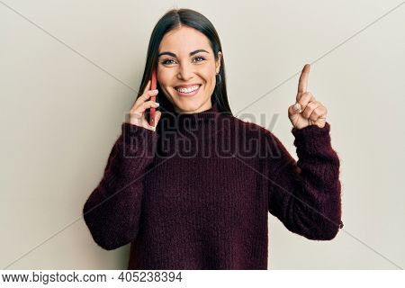 Young brunette woman having conversation talking on the smartphone smiling with an idea or question pointing finger with happy face, number one