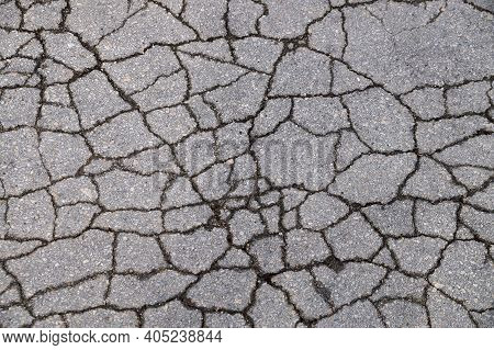 Gray Texture Of Cracked Asphalt For Background Close-up