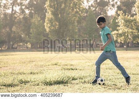Focused Black Haired Boy In Glasses Kicking Soccer Ball On Grass In City Park. Full Length, Wide Sho
