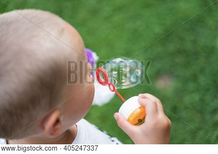 Overhead View Of A Toddler Child Blowing Soap Bubbles Outside.