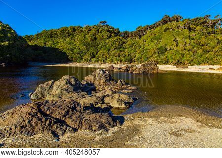 South Island, New Zealand. The road to Knight's Point Lookout is an unforgettable landscape.  Pacific coast at low tide. Sunset. Puddles of ocean water on the shore
