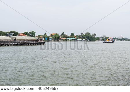 A Tug Boat Is Towing The Large Cargo Boat Which Contains The Sand For Delivery To The Construction S