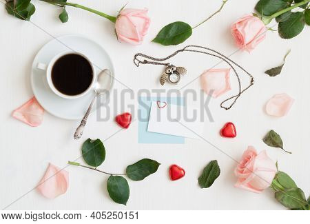 Valentines day background - cup of coffee, peach roses, blank card, owl shaped clock, heart shaped candies on white background, Valentines card, Valentines still life