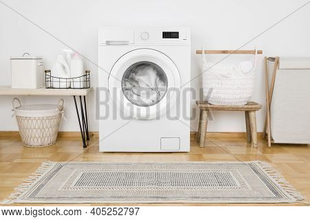 Laundry Room With Loaded Washing Machine, Detergent Bottles And Textile