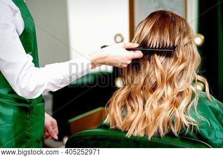 Back View Of Hairdresser Combing Wavy Hair Of A Young Blonde Woman In A Beauty Salon