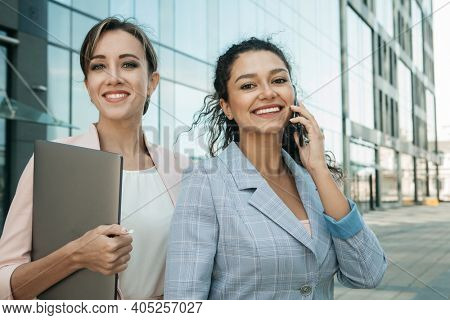 Business, people, tehnology and lifestyle concept: Two business women. One is holding a laptop, the other is talking on the phone. Mixed races. Caucasian woman and African woman. Outdoor shoot.