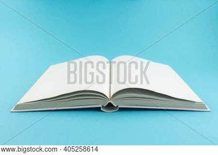 Open Hardcover Book With Blank White Pages On Blue Background