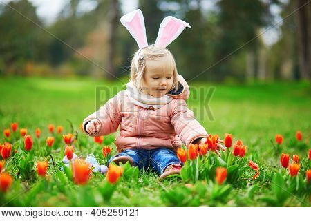 Cute Little Girl Wearing Bunny Ears Playing Egg Hunt On Easter. Toddler Looking For Colorful Eggs In