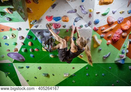 Caucasian Young Woman Bouldering In Indoor Climbing Gym, Ready To Make Challenging Move
