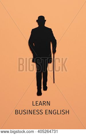 the silhouette of an elegant man, wearing hat and using a walking cane, cutout on a black paperboard, and the text speak business english on a pale orange background