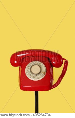 a red landline rotary dial telephone on the top of a black tubular stand, on a yellow background, with some blank space on top
