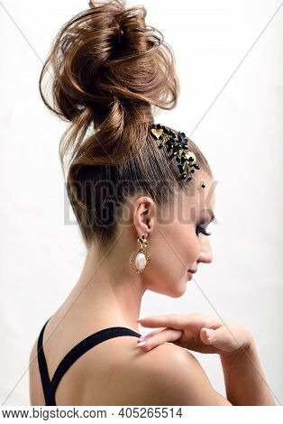 Attractive Woman With Evening Makeup And High Hair Bun. Beauty Portrait With Jewelry In Hair