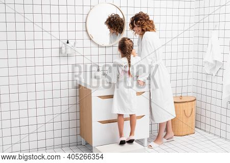 Curly Woman In Bathrobe Looking At Child Near Sink In Modern Bathroom