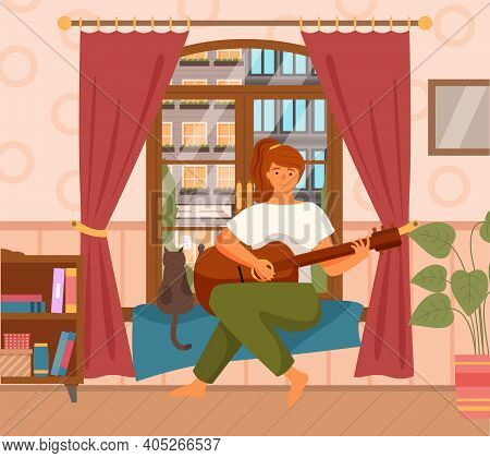 Woman Is Playing Guitar Sitting In Armchair. Musician Composes Songs And Sings At Home Near Window.