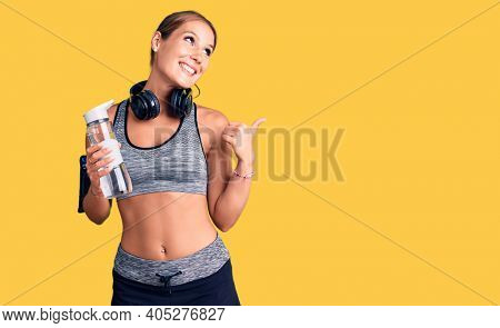 Young beautiful hispanic woman wearing sportswear holding water bottle pointing thumb up to the side smiling happy with open mouth