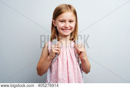 Portrait of primary school girl with backpack on gray background