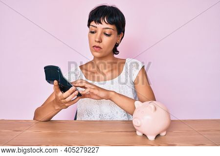 Beautiful brunettte woman caculating money savings relaxed with serious expression on face. simple and natural looking at the camera.