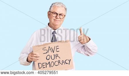 Senior grey-haired man wearing business clothes holding save our democracy protest banner smiling happy and positive, thumb up doing excellent and approval sign