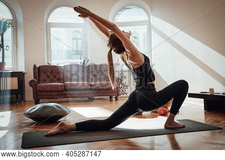 Atmospheric Living Room With Sunbeams And Relaxed Sportswoman In Black Clothing Works Out Doing Yoga