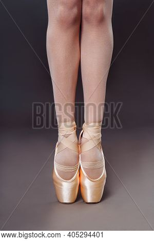 Close-up Of Ballerine Feet In Pointe Shoes On Grey Background. Ballerina Is Standing On The Hips. St