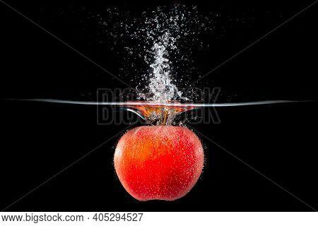 Red Apple Is Falling Into Splashing Water
