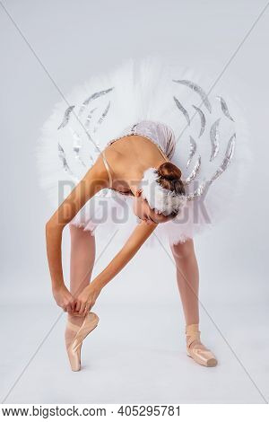 Professional Legs Of A Young Ballerina Who Puts On Pointe Shoes Isolated On A White Background In Th