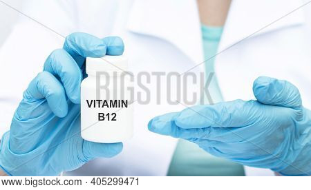 Doctor Holding A White Jar On Which The Text With Vitamin B12, Medical Concept
