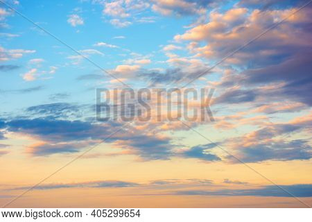 Cloudscape In Summer At Sunrise. Clouds On The Blue Sky In Yellow And Pink Morning Light. Idyllic We