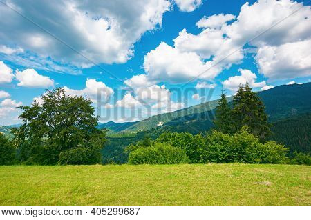 Mountainous Rural Landscape In Summertime. Trees On The Hillside Meadow. Clouds On The Blue Sky Abov
