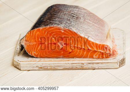 Raw Salmon On Cutting Board. Piece Of Fresh Salmon On A White Board.