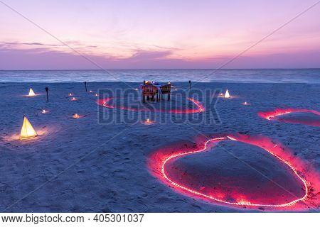 Beautiful Table Set Up For A Romantic Meal On The Beach With Candles And Chairs And Heart Shapes In