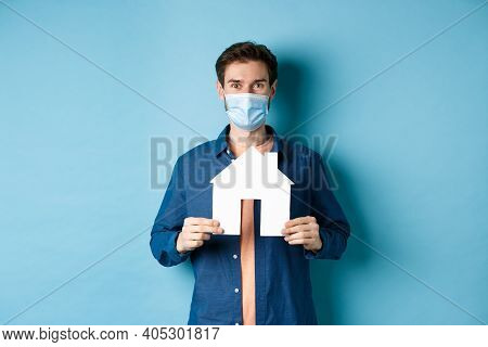 Real Estate And Quarantine Concept. Happy Young Man In Medical Mask Showing House Cutout, Buying Pro