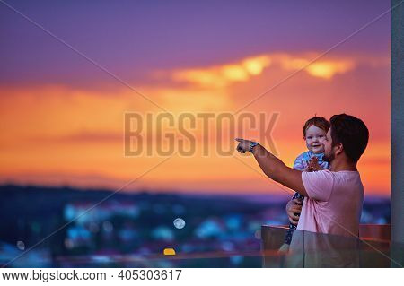 Happy Father And Baby Watching The City On Sunset At The Rooftop Balcony With Glass Balustrade