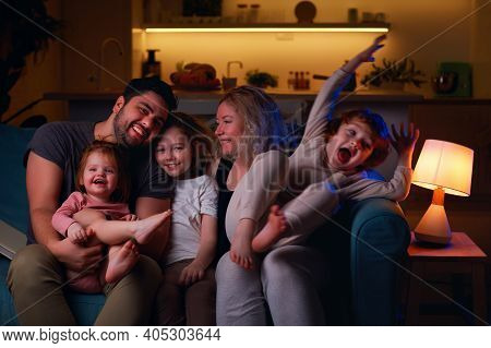 Cheerful Family Having Fun Together At Cozy Home In The Evening