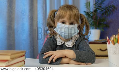 Sad Child Girl Pupil In Medical Mask Doing School Homework At Home. Video Call By Webcam On Internet