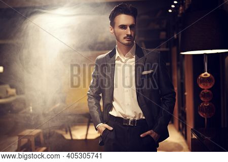 Handsome brunet man in an elegant suit stands in a luxury apartment. Mafia. Male beauty, fashion.