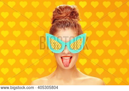 Beauty and pin-up style. Portrait of an exciting pretty woman posing in paper sunglasses in pin-up style on a yellow background. Makeup and cosmetics. Studio shot. Copy space.