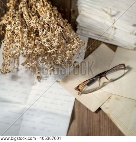 Open Handwritten Letter And Pile Of Old Letters In Envelopes, Eyeglasses And A Dry Bouquet Of Flower
