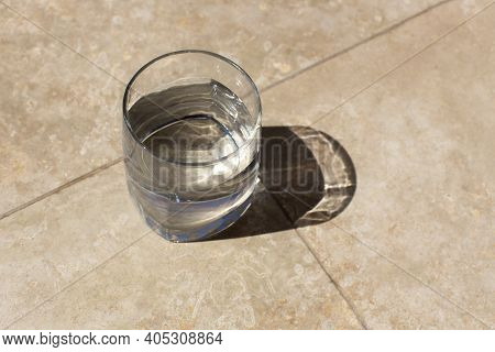 Glass Of Still Water On Table In Harsh Sunlight, Long Shadows, On Table, Top View. Health Care Conce