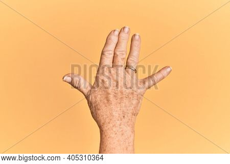 Senior caucasian hand over yellow isolated background greeting doing vulcan salute, showing back of the hand and fingers, freak culture