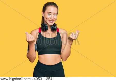 Beautiful blonde woman wearing gym clothes and using headphones doing money gesture with hands, asking for salary payment, millionaire business