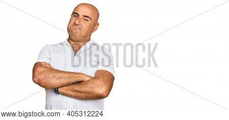 Mature middle east man with mustache wearing casual white shirt looking to the side with arms crossed convinced and confident
