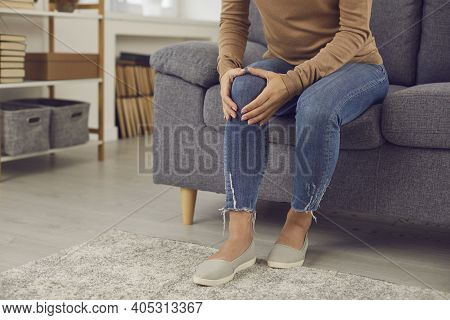 Woman Who Has Rheumatic Disorder Or Has Hurt Knee In Home Accident Massaging Her Knee Cap