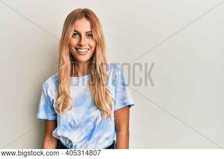 Beautiful blonde young woman wearing tye die tshirt with a happy and cool smile on face. lucky person.