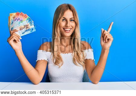 Beautiful blonde young woman holding swiss franc banknotes smiling happy pointing with hand and finger to the side