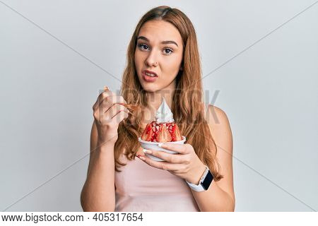 Young blonde woman eating strawberry ice cream clueless and confused expression. doubt concept.