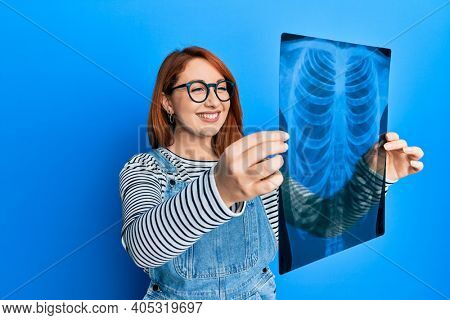 Beautiful redhead woman holding chest radiography smiling with a happy and cool smile on face. showing teeth.