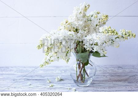 White Lilac Bouquet In Glass Vase On Wooden Table. Spring Branches Of Blooming Lilac Festive Bouquet