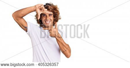 Young hispanic man wearing casual white tshirt smiling making frame with hands and fingers with happy face. creativity and photography concept.